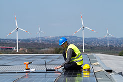 Worker installing solar panels with wind turbines in backdrop