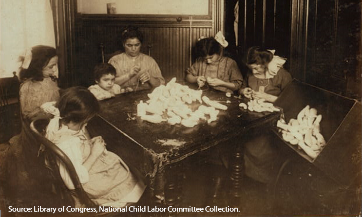 In 1908, children and their mother work making doll legs after school and often until 10 pm, New York.